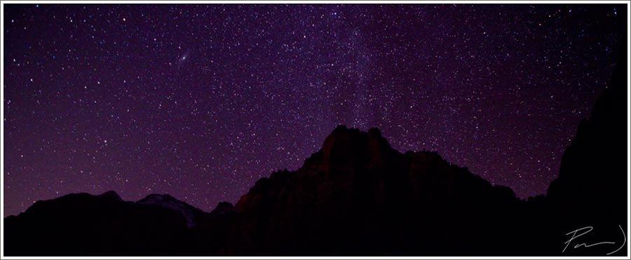 A stitched panorama of the beautiful star-filled sky over the canyon walls at Zion National Park.